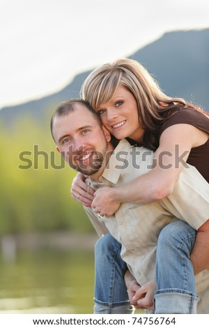 young attractive couple piggyback ride at a mountain lake - stock photo