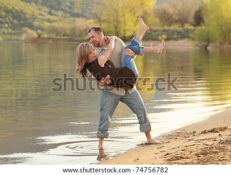 young attractive couple playing together on beach