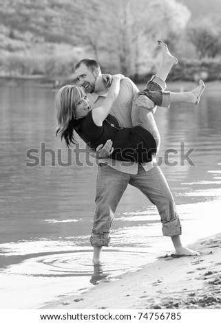 young attractive couple playing together on beach - stock photo