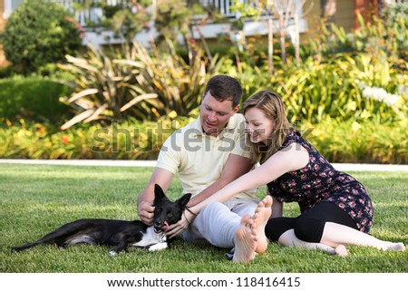 Young attractive couple playing with their dog - stock photo
