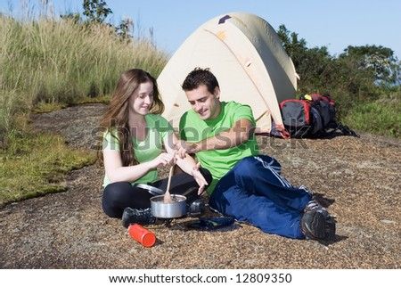 Young attractive couple preparing a meal while camping in front of their tent - stock photo