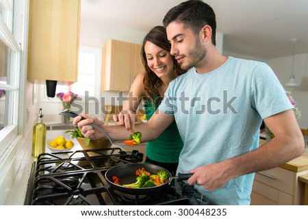 Young attractive couple preparing dinner on a date saving money by cooking at home - stock photo