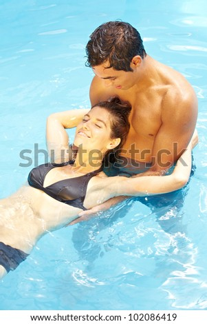 Young attractive couple relaxing together in blue swimming pool