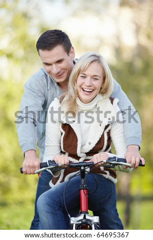 Young attractive couple rides a bicycle in the park - stock photo