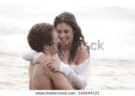 Young attractive couple sharing a happy moment at the beach  - stock photo
