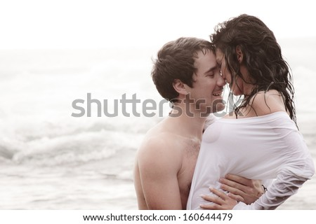 Young attractive couple sharing a moment at the beach  - stock photo
