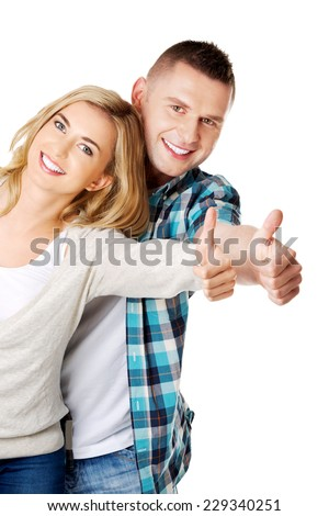 Young attractive couple showing thumbs up - stock photo