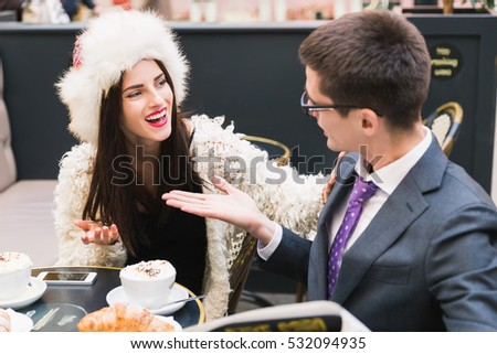 Young attractive couple sitting in a cafe, and having discussion
