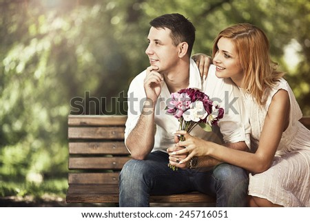 Young attractive couple sitting on bench in the park, embracing and looking and look in the same direction - stock photo