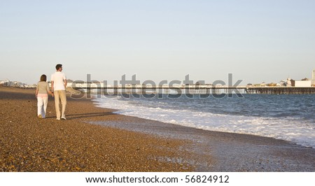 Young attractive couple walking along beach, pier in background - stock photo