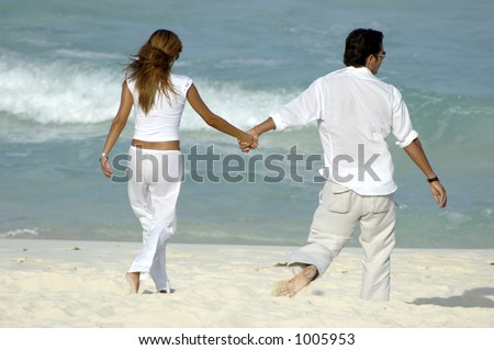 Young attractive couple walking along the beach holding hands - stock photo