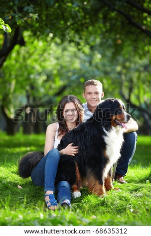 Young attractive couple walks his dog - stock photo