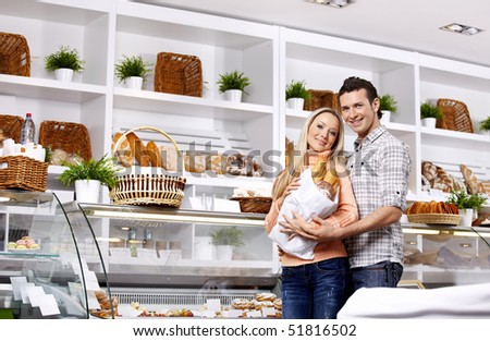 Young attractive couple with a package of rolls in shop - stock photo