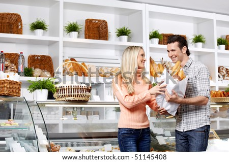 Young attractive couple with bread in shop - stock photo