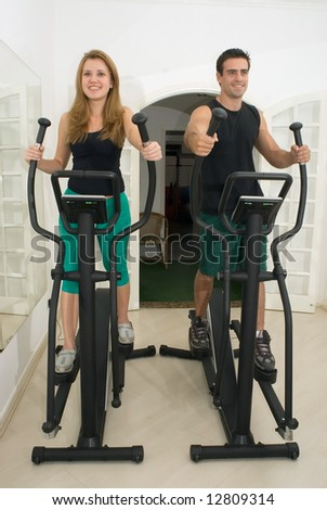 Young, attractive couple working out at the gym together. Vertically composed shot taken from directly in front of the couple. - stock photo