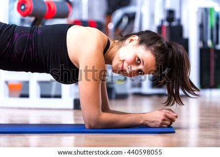 Young, attractive, cute athlete girl in sportswear while planking at the gym on a mat and expressing happiness, health and wellness.