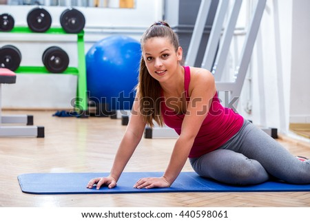 Young, attractive, cute athlete girl in sportswear while resting on the floor at the gym after a healthy workout expressing vitality, strength and healthy lifestyle. - stock photo