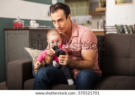 Young attractive dad playing video games at home while taking care of her baby girl - stock photo