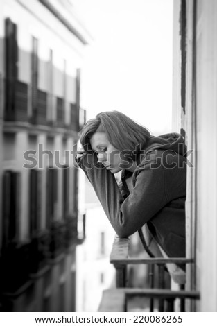 young attractive depressed woman suffering depression and stress outdoors at home balcony terrace window in pain feeling sad and desperate in urban background in black and white - stock photo
