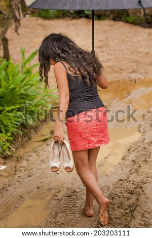 Young attractive Ecuadorian lady walking through mud with bare feet