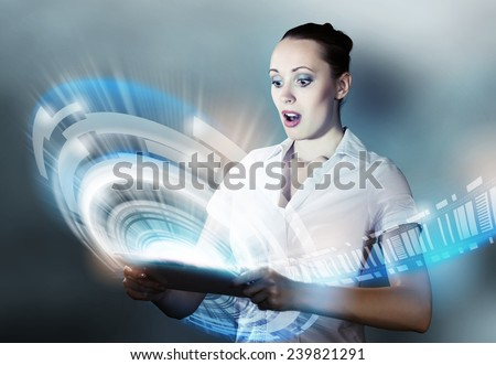 Young attractive emotional woman using tablet pc - stock photo