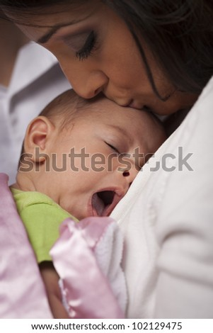 Young Attractive Ethnic Woman Holding Her Yawning Newborn Baby. - stock photo