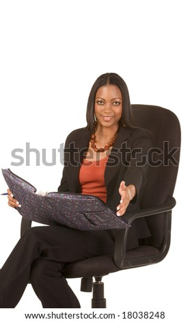 Young attractive ethnic woman in business suit sits in office chair with folder on her lap and stretches her hand towards viewer - stock photo
