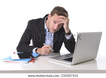 young attractive European businessman working in stress at office desk computer laptop suffering headache, worried and frustrated isolated on white background