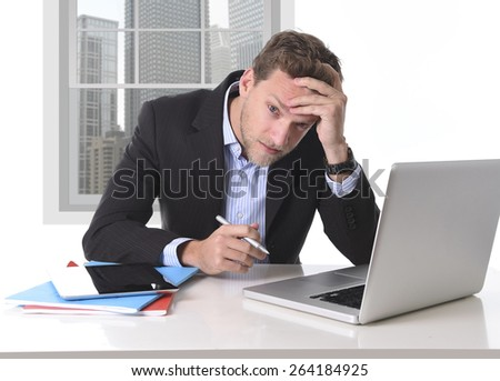 young attractive European businessman working in stress at office desk computer laptop suffering headache, worried and frustrated looking depressed and overwhelmed for too much work - stock photo