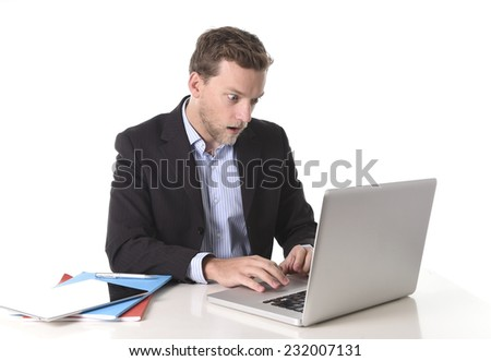 young attractive European businessman working in stress at office desk computer looking monitor in shock worried about sales figures isolated on white - stock photo