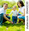 Young attractive family in the summer park - stock photo