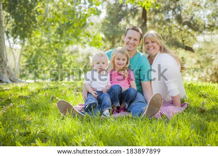 Young Attractive Family Portrait Enjoying the Park. - stock photo