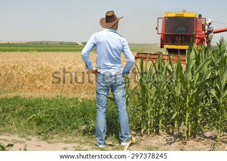 Young attractive farmer with cowboy hat standing in the field and looking at combine harvester - stock photo