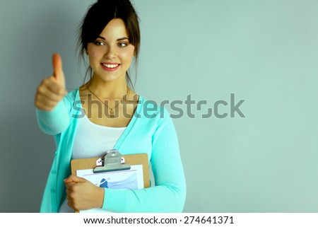 Young attractive fashion designer holding folders - stock photo