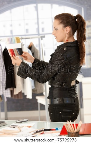 Young attractive fashion designer working in bright office, looking at colour samples.? - stock photo