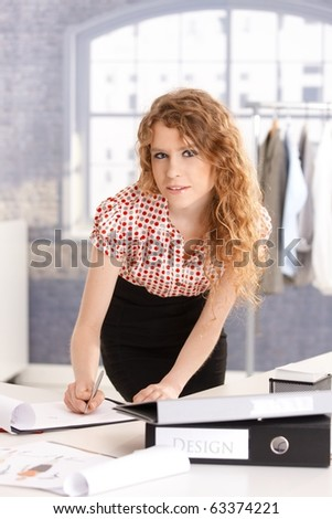Young attractive fashion designer working in office at desk.? - stock photo