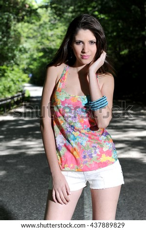 Young attractive fashion model posing on the way, under the trees. - stock photo
