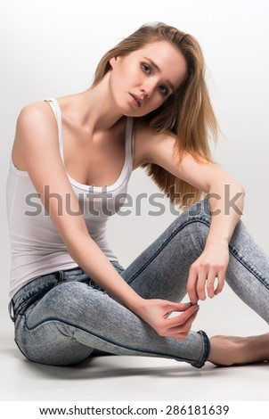 Young attractive fashionable deplorable model sits over white background - stock photo
