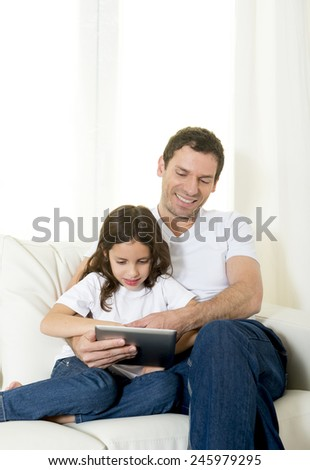 young attractive father sitting on couch with 7 years old sweet little girl daughter using digital tablet pad at home smiling happy together in children technology concept