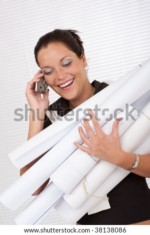 Young attractive female architect holding plans and telephone at the office