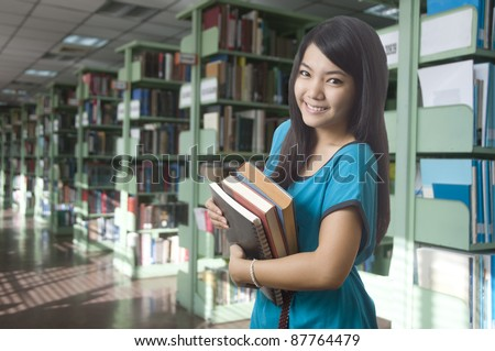 Young attractive female Asian student holding her school books in the library - stock photo