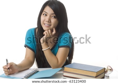 Young attractive female Asian student sitting at her desk and thinking