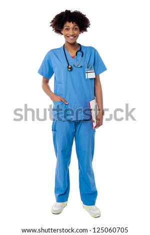 Young attractive female doctor is standing with the clipboard. Full length over white. - stock photo