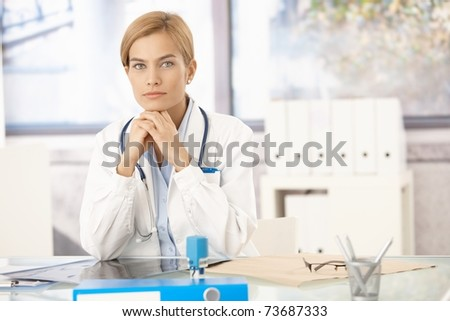 Young attractive female doctor sitting at desk in office.? - stock photo