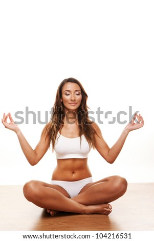 Young attractive female doing yoga exersise on white background - stock photo