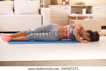 Young attractive female doing yoga in her living room. - stock photo