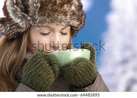 Young attractive female dressed up warm in coat, fur-hat and gloves, drinking hot tea, eyes closed.? - stock photo