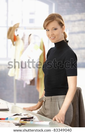 Young attractive female fashion designer standing at office desk, smiling.? - stock photo