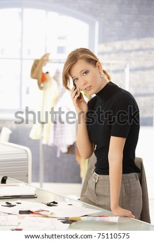 Young attractive female fashion designer talking on mobile phone in office, looking at camera.? - stock photo