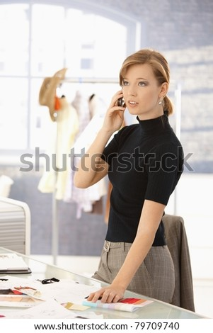 Young attractive female fashion designer talking on mobile phone, selecting color samples on office desk.? - stock photo